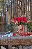 Advent arrangement of four lit red candles in basket