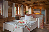 Embroidered blanket on bed in rustic bedroom