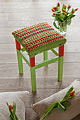 Crocheted seat cover on red and green stool