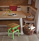 Gehäkelter Sitzbezug auf einem rot-grünen Hocker am Esstisch