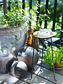 Stone ball, planter, metal stand and collection of flotsam on balcony