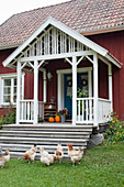 Hühner vor der Treppe zur Veranda eines Schwedenhauses