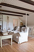 Two white armchairs in rustic living room with wooden roof beams and sloping wall