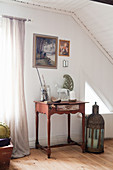 Large lantern on floor next to small red table with vintage accessories