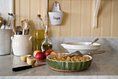Apples and pie in dish on marble kitchen worksurface