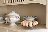 Egg rack, soup tureen and old crockery on kitchen dresser