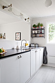 Simple white kitchen with black worksurface and serving hatch