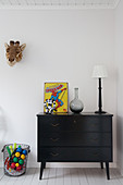 Spiderman poster on top of black chest of drawers in child's bedroom