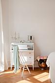 Scandinavian spoke-back chair at white bureau in bedroom