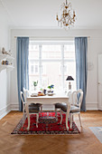 Classic dining table with medallion chairs on Oriental rug in front of window