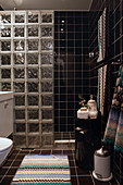 Glass brick shower screen in bathroom with black tiles