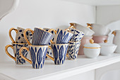 Blue-patterned mugs with gilt handles on shelf