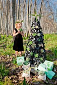 Girl standing next to stylised Christmas tree decorated with leaves and succulents amongst bare trees in sunny woodland