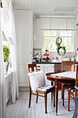 Antique table and chairs in Scandinavian country-house kitchen