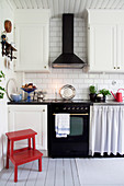 Red stool in Scandinavian country-house kitchen with classic cooker