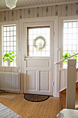 Front door and lattice windows in Scandinavian country-house-style foyer