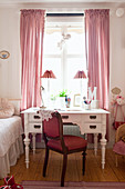 Red upholstered chair and antique desk below window in child's bedroom