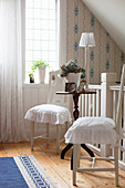 Two white chairs with ruffled seat cushions at antique side table