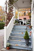 Autumn decorations on steps leading to veranda in Swedish country-house style