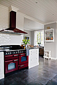 Red cooker in large, white country-house kitchen with grey floor