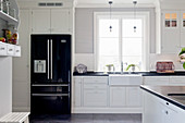 Black fridge in white country-house kitchen with panelled cabinets