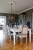 Tisch und Stühle im gustavianischen Stil im Esszimmer mit grauer Blümchentapete