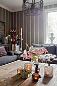 Rosa Lilien und Kerzendeko auf dem Couchtisch im Wohnzimmer