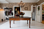 Old wooden table in large foyer with white wainscoting and brown wallpaper