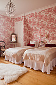 Twin beds in bedroom with red Toile de jouy wallpaper