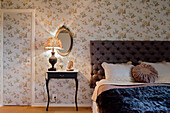 Floral wallpaper on walls and door in vintage-style bedroom