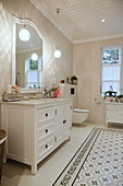 Classic washstand in white bathroom with patterned tiles