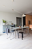 Various chairs around dining table in front of plywood kitchen