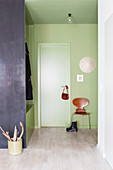 Green foyer with coat rack used as partition