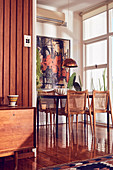 Wooden table and vintage chairs on shiny wooden floor in dining area