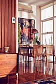 Holztisch und Vintage Stühle auf glänzendem Holzboden im Essbereich