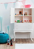 White-painted antique cabinet converted into dolls' house in retro girl's bedroom