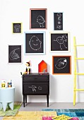 Children's drawings on blackboards with colourful frames on white wall