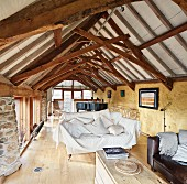 Grand piano in bright lounge area of rustic attic with restored roof structure
