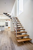 Modern staircase with wooden treads in modern interior with kitchen in background