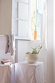 Melons and flowers in white bowl on loose-covered stool below open window