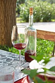 Glass of wine next to bottle of wine on garden table