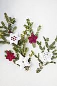 Verschiedene gehäkelte DIY-Anhänger an grünen Tannenzweigen