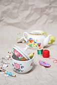 Sewing supplies in old teapot and sugar bowl