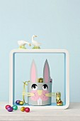 Paper Easter basket with bunny face in shelving module