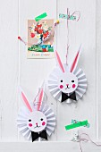 Vintage greetings card and Easter bunnies on paper rosettes decorating wall