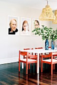 Portrait photos above the dining table with red chairs and flowers