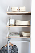 Storage baskets on shelves above clothes rail