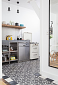 Patterned floor and stainless steel cabinets in open-plan kitchen