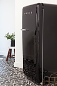 Black retro fridge on patterned floor tiles