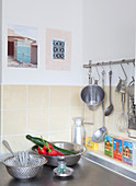 Every day still-life arrangement in kitchen with metal bowls and hooks on rail